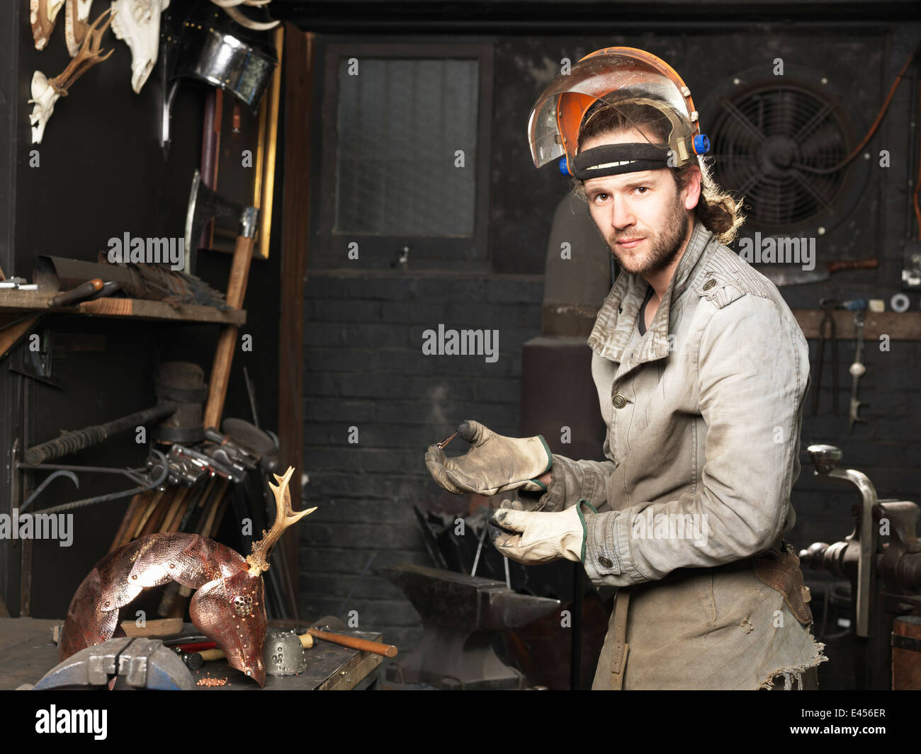 Portrait of blacksmith with a copper nail in workshop - Stock Image
