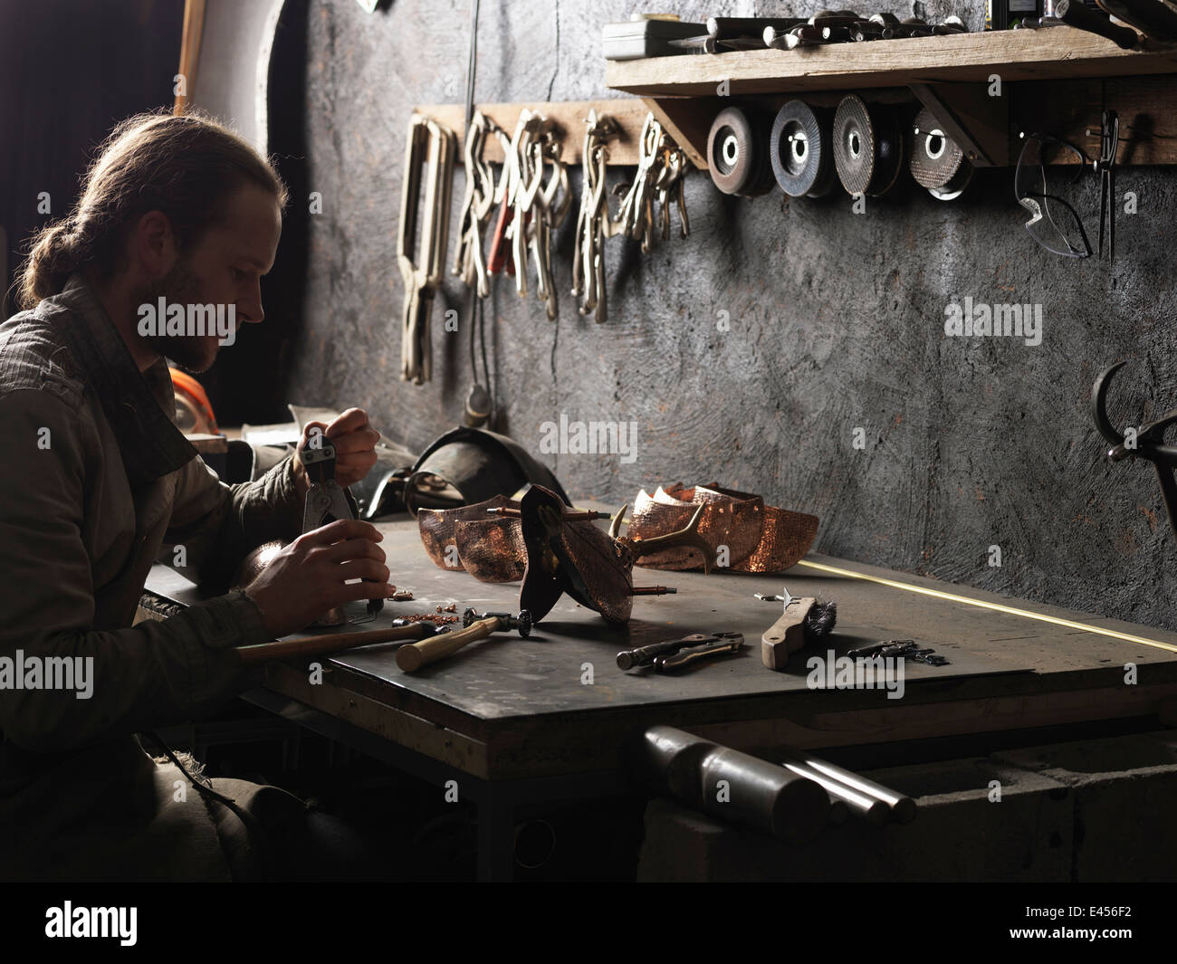 Blacksmith working with copper rivets in workshop - Stock Image