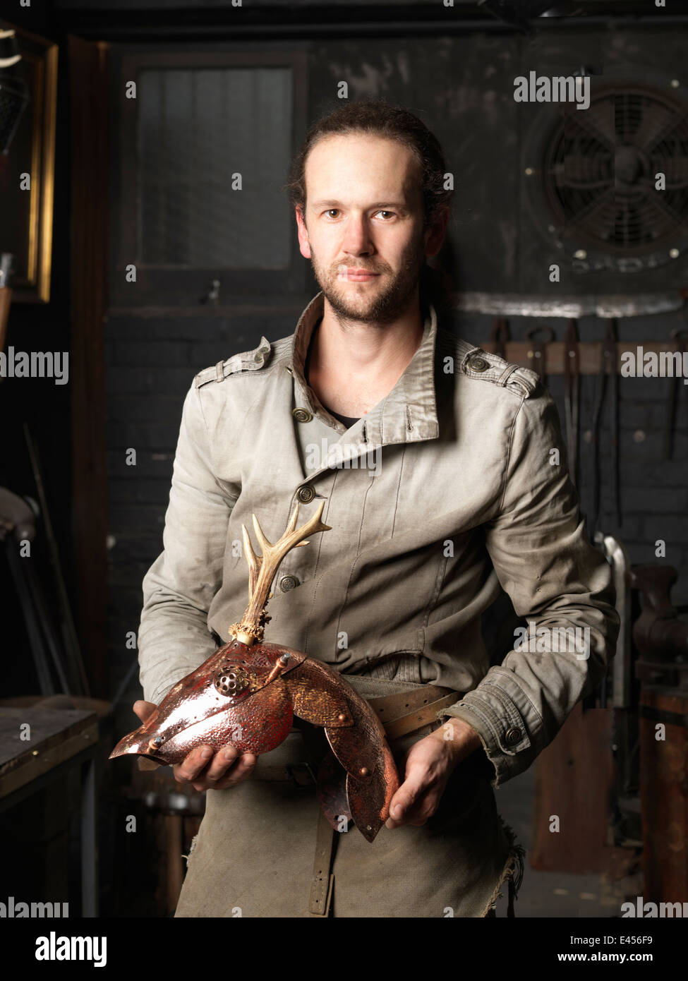 Portrait of blacksmith with a copper deer sculpture - Stock Image