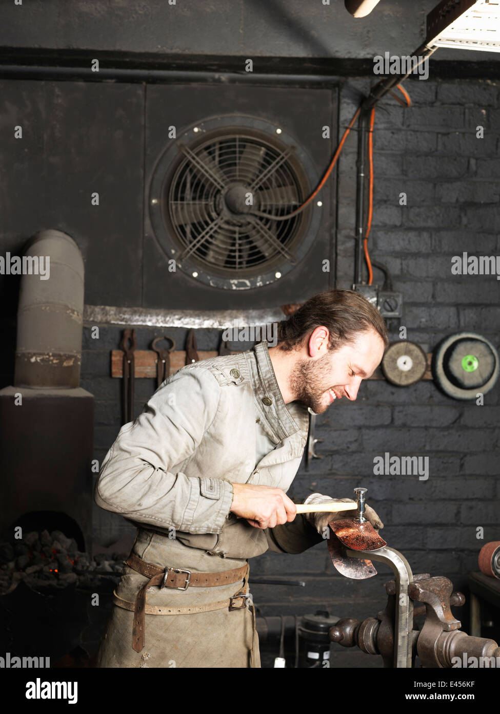 Blacksmith hammering copper in workshop - Stock Image