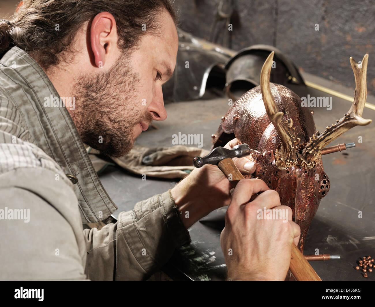 Blacksmith hammering copper on deer sculpture in workshop - Stock Image