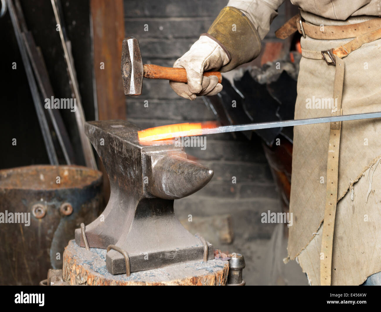 Cropped image of blacksmiths hammering a red hot metal rod - Stock Image