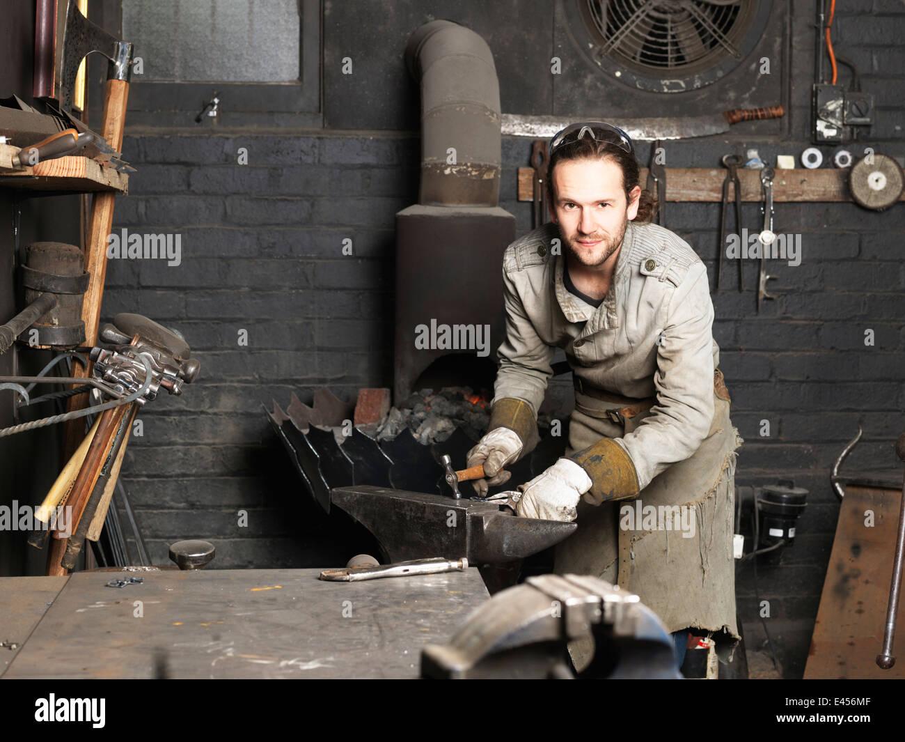 Portrait of blacksmith hammering on workshop anvil - Stock Image