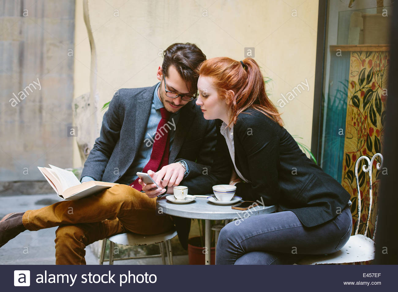 Couple sitting in cafe - Stock Image