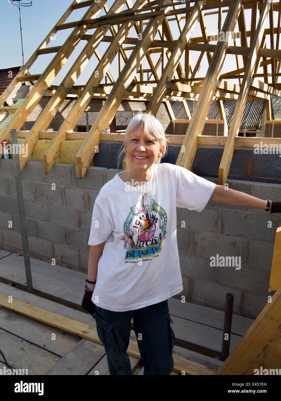 self building house, senior female self-builder on scaffolding at roof level - Stock Image