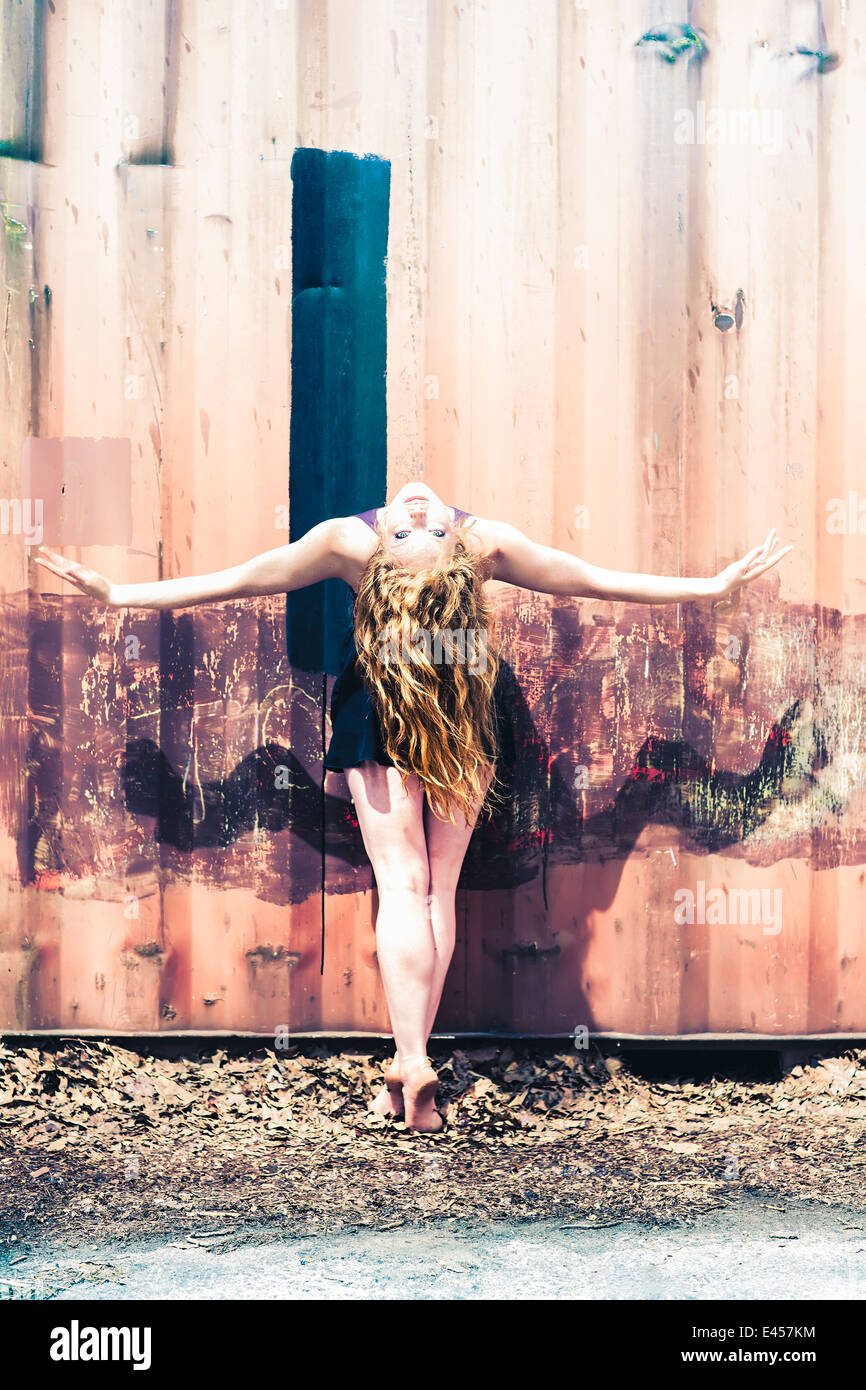 Modern dancer striking a pose in front of an abandoned shipping container - Stock Image