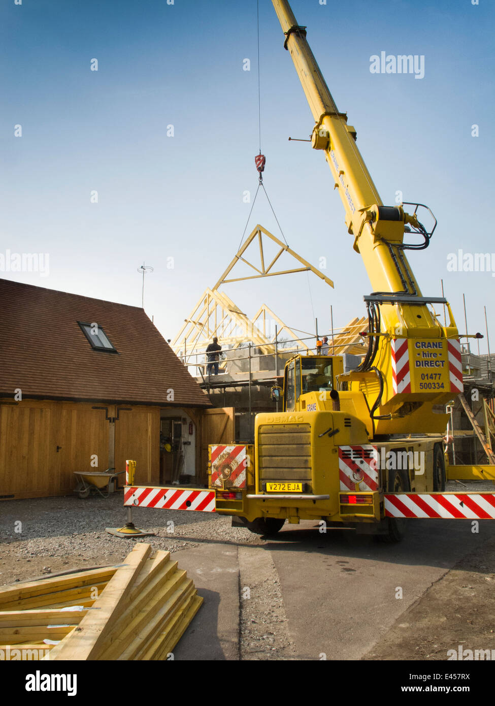 self building house, constructing roof, lifting roof trusses with rented crane - Stock Image