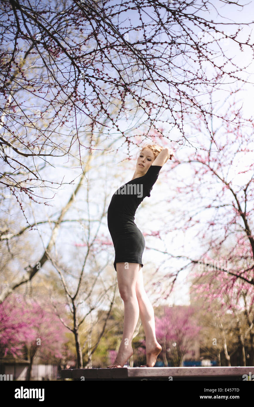 Modern dancer striking a pose in a urban park - Stock Image