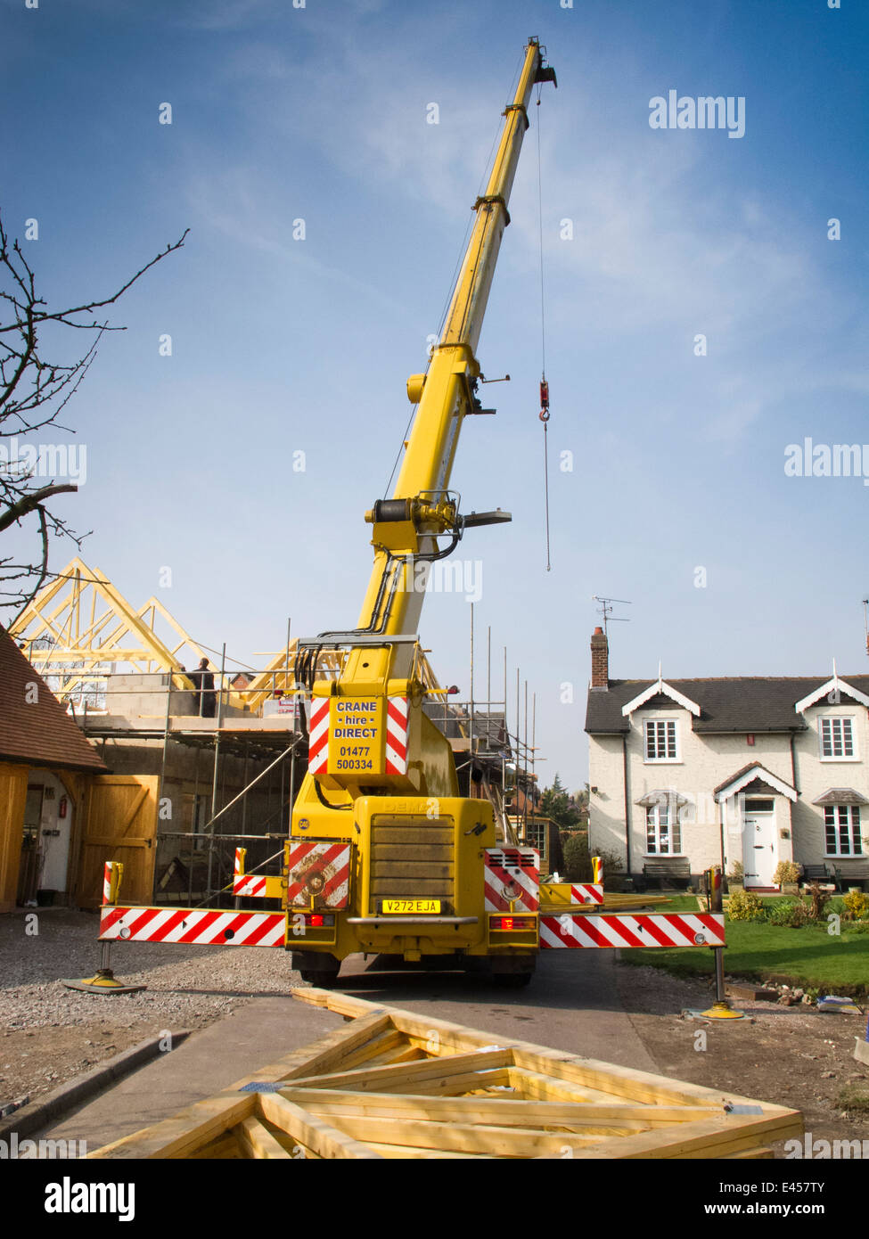 self building house, constructing roof, lifting roof, trusses with rented crane - Stock Image