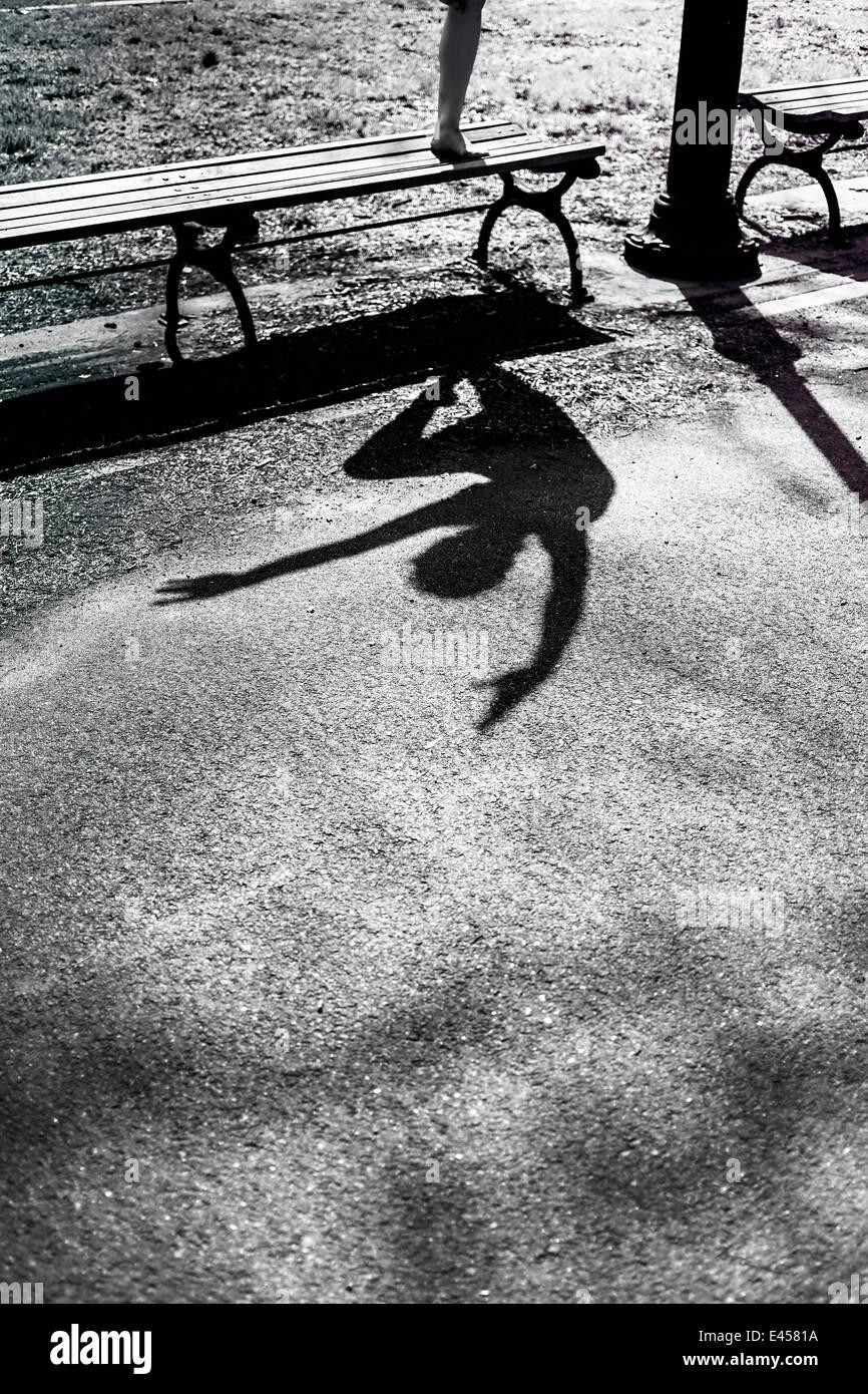 Modern dancer striking a pose in a urban park, shadow - Stock Image