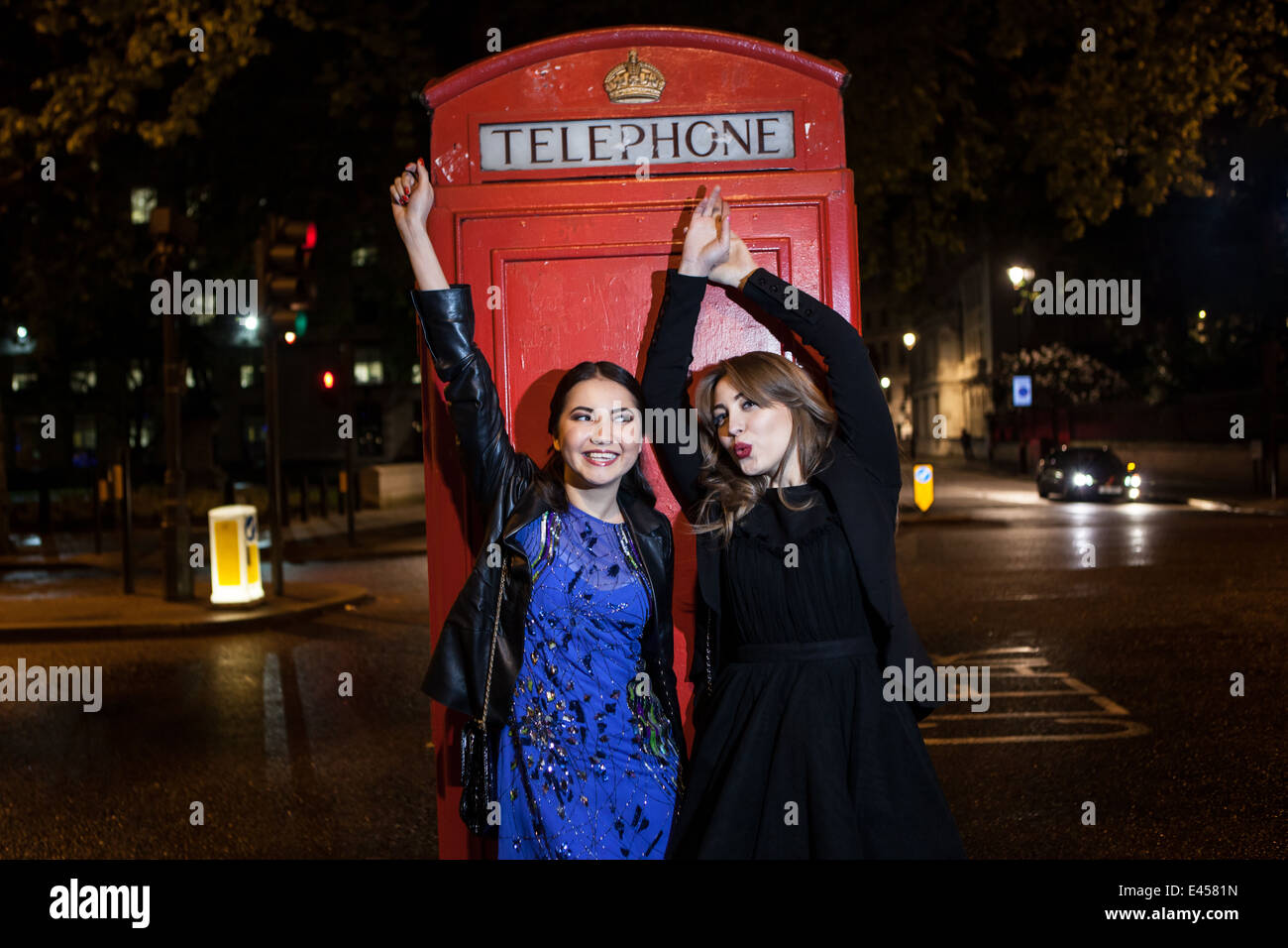 Two young female friends dancing in front of red phone box at night, London, UK - Stock Image