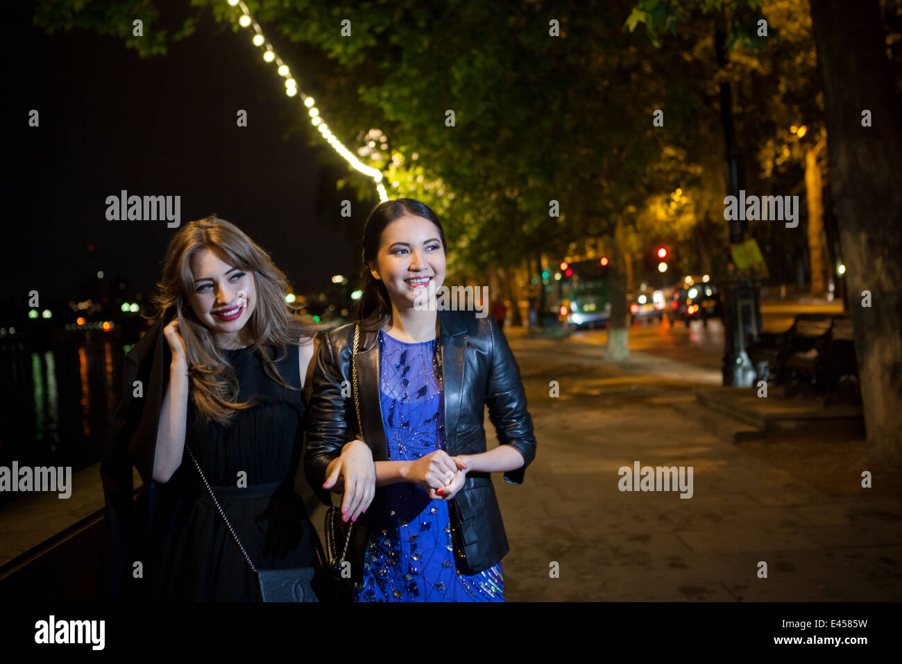 Two female friends strolling along riverside at night - Stock Image