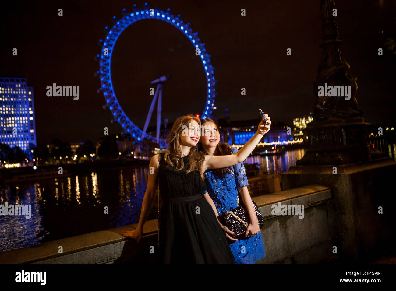 Two young female friends taking self portrait at night, London, UK - Stock Image