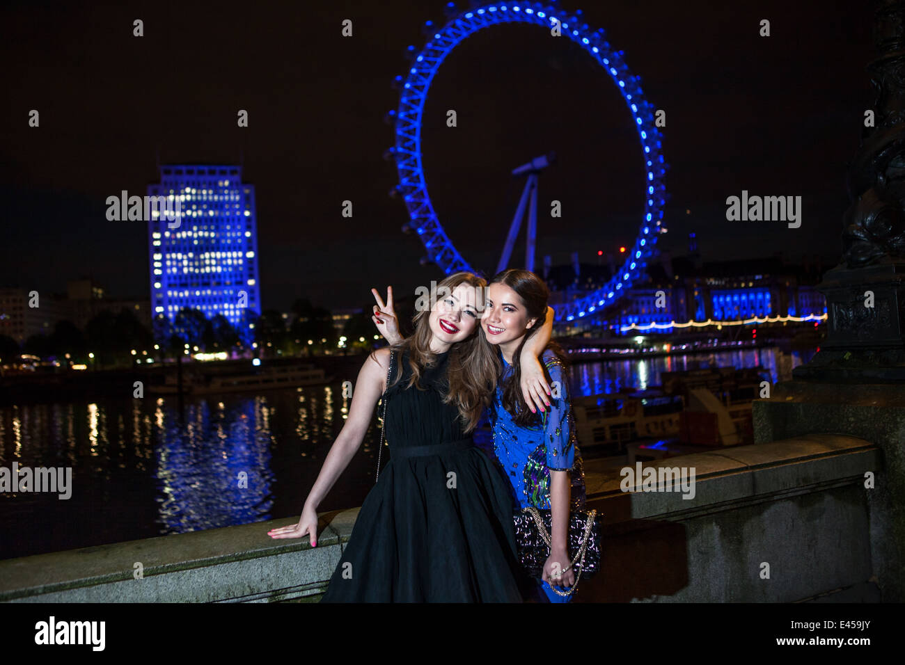 Portrait of two female friends posing with London Eye at night, London, UK - Stock Image