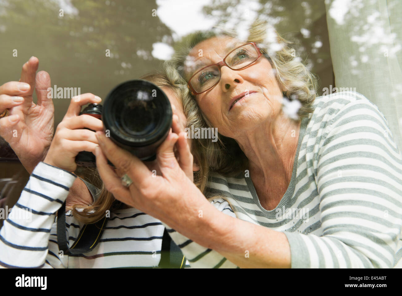 Grandmother teaching granddaughter camera usage Stock Photo