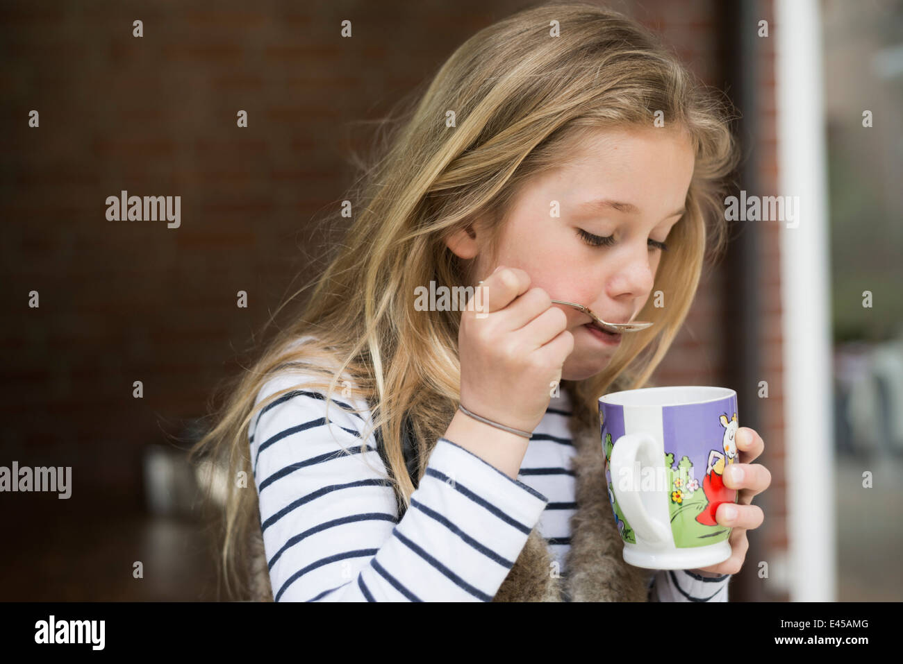 Girl spooning drink from mug - Stock Image