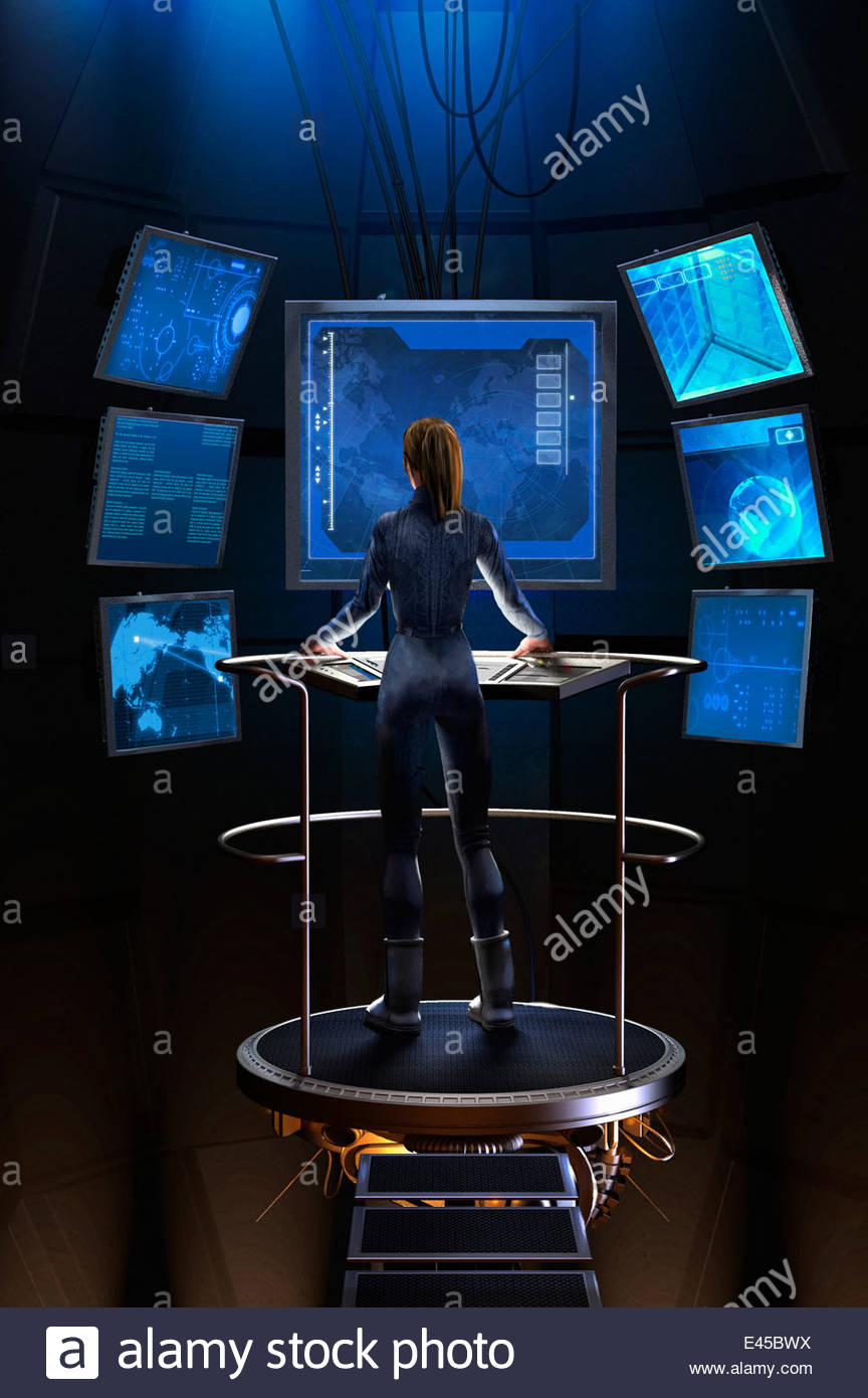 Woman standing at control panel in futuristic control room - Stock Image