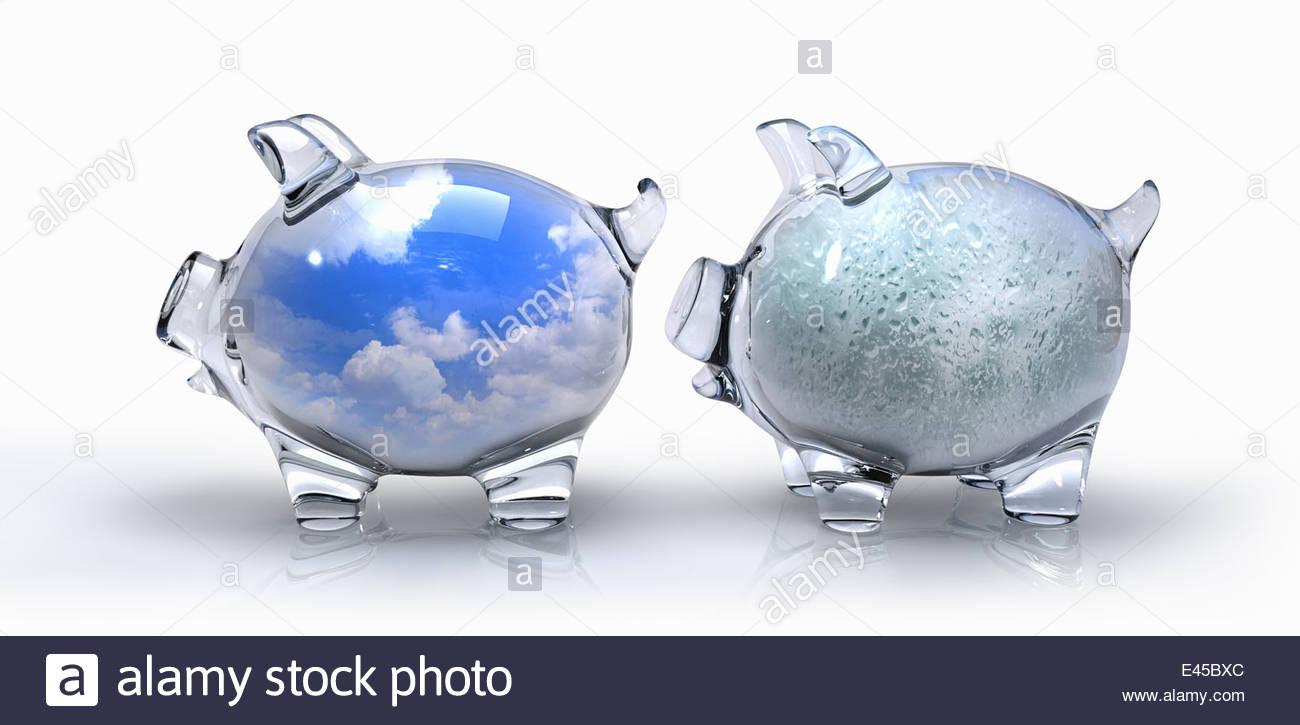Transparent blue sky piggy bank contrasting with rain piggy bank - Stock Image
