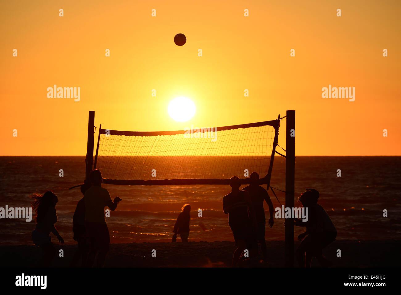 Silhouette of Teen females playing beach volleyball at sunset Bradenton Beach Florida bhz - Stock Image