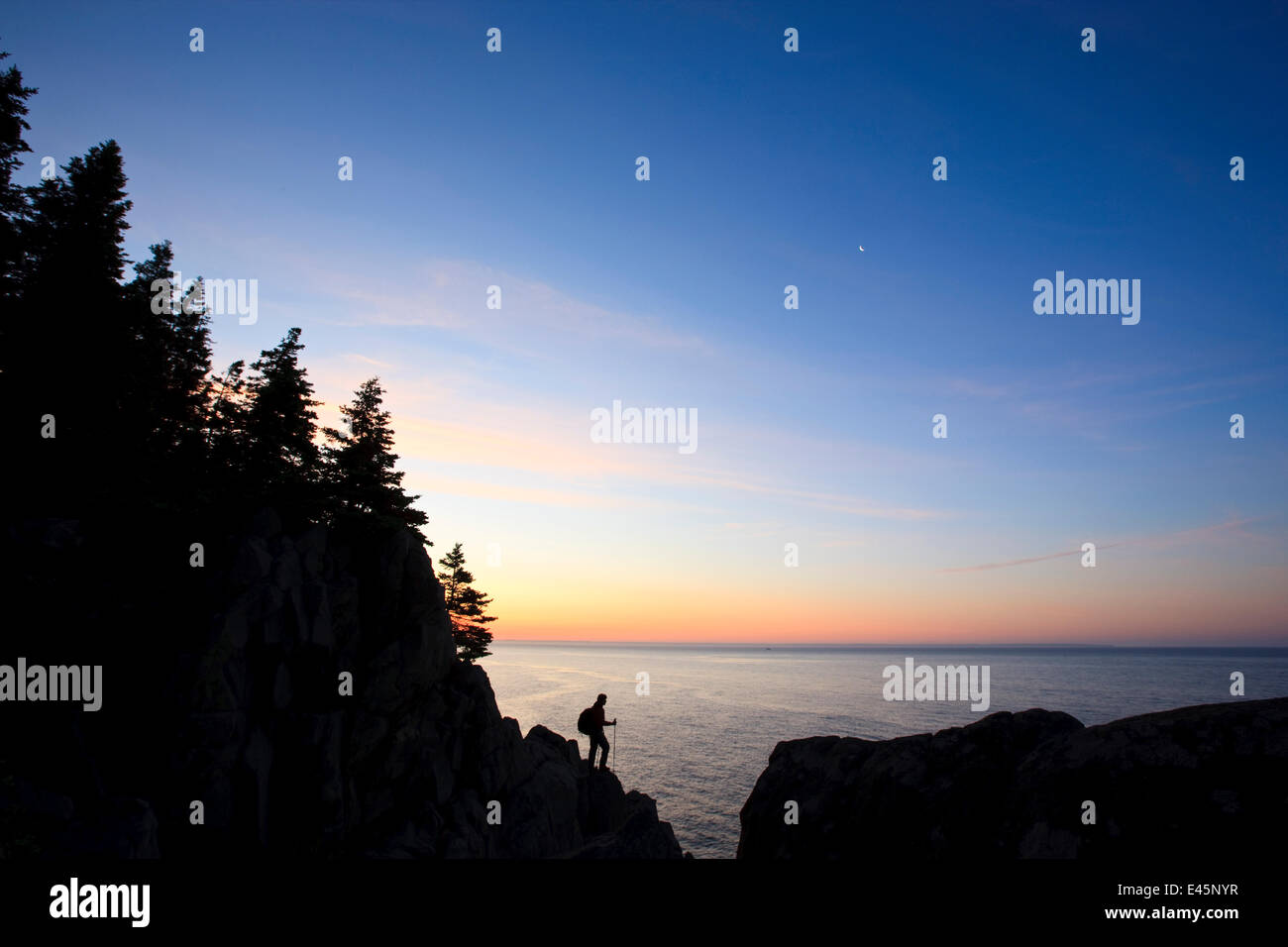 Lone hiker at sunrise on the Bold Coast trail in Cutler, Maine, USA, June 2009. Model released. - Stock Image