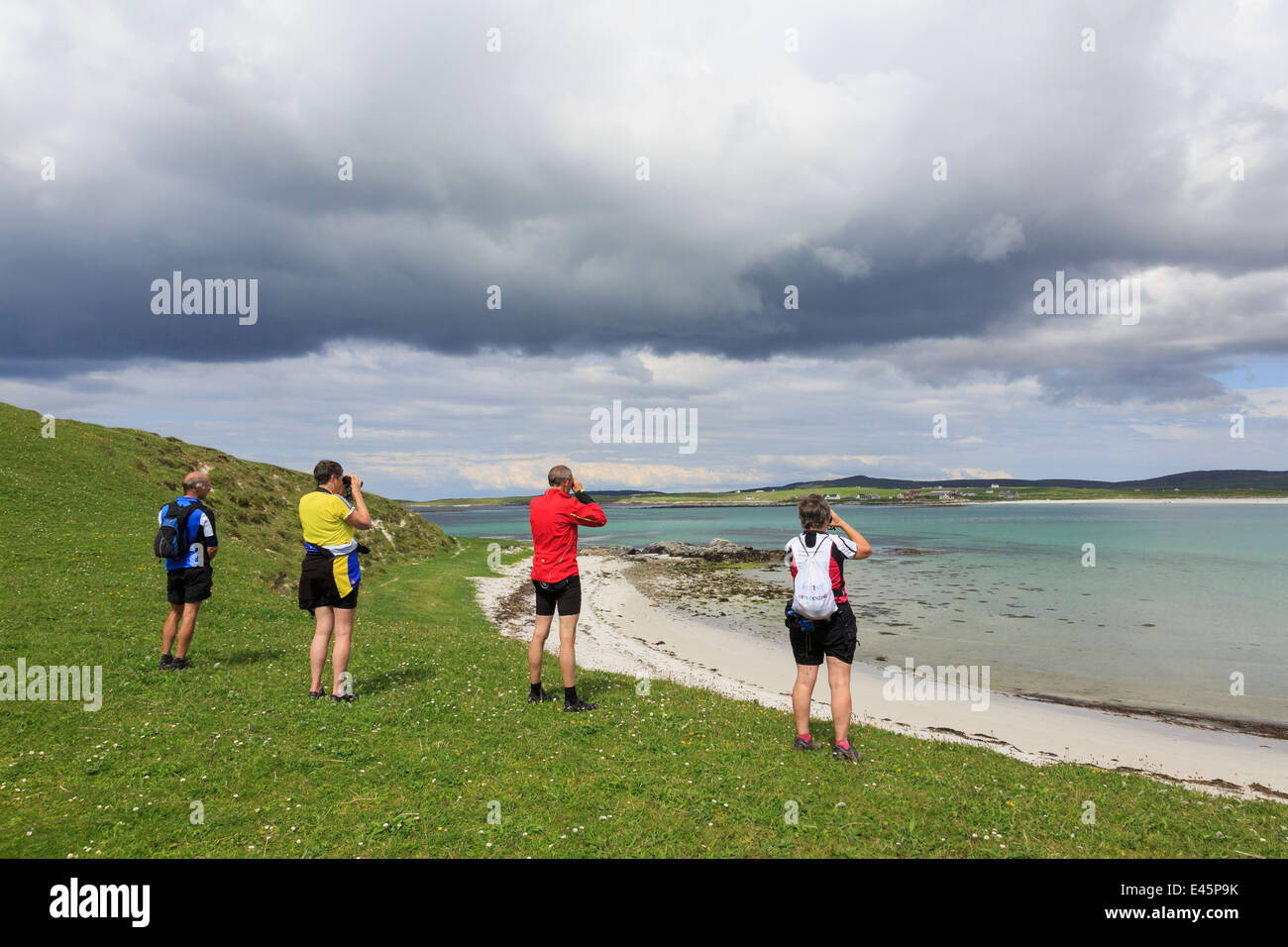 Birdwatchers using binoculars to watch birds on Scottish west coast. Balranald RSPB Nature Reserve North Uist Western - Stock Image