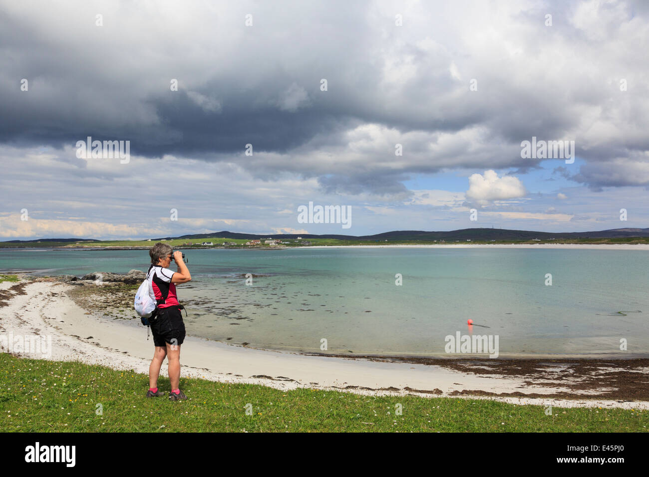 Female birdwatcher using binoculars to watch birds on west coast. Balranald RSPB Nature Reserve North Uist Outer - Stock Image