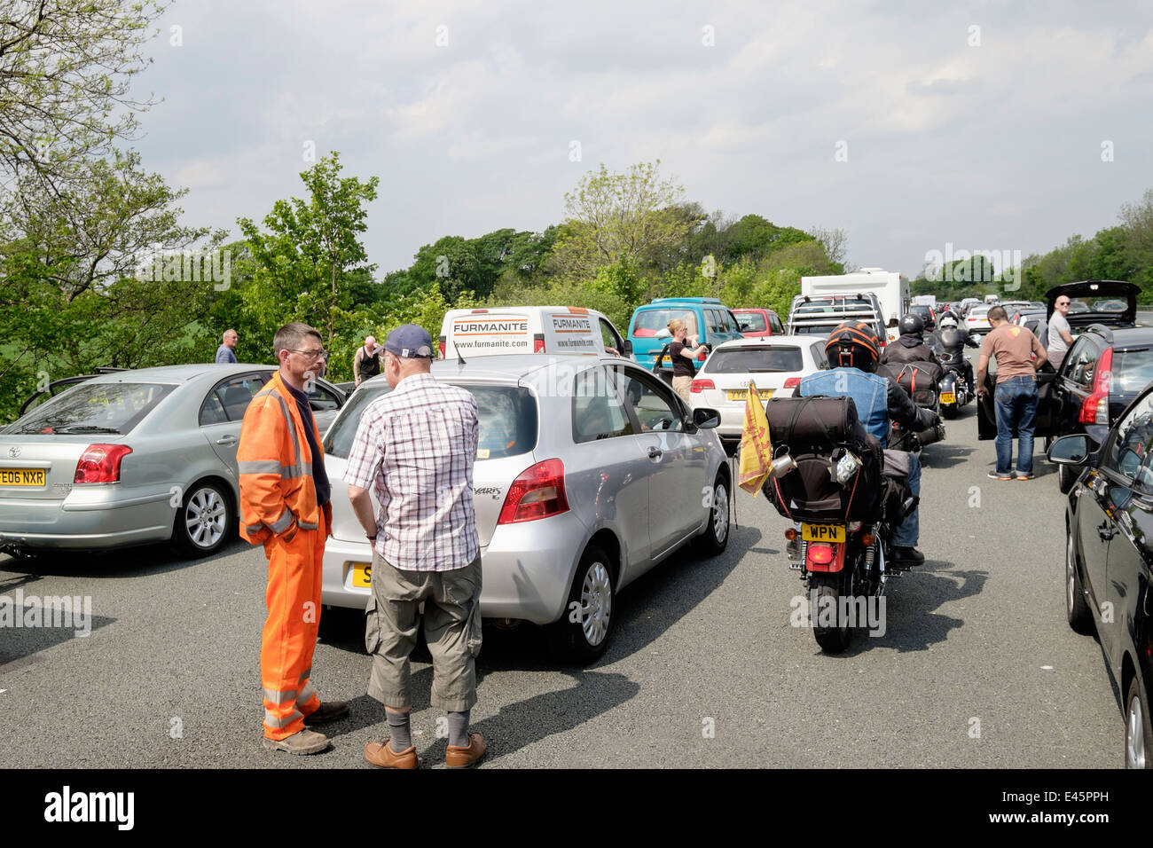 Motorbikes driving riding through stationary vehicles in a traffic jam with people standing on carriageway on M6 - Stock Image