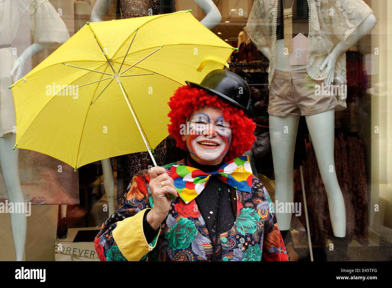 Lady clown holding yellow umbrella in front of fashion shop window, street party, Munich, Upper Bavaria, Germany, - Stock Image