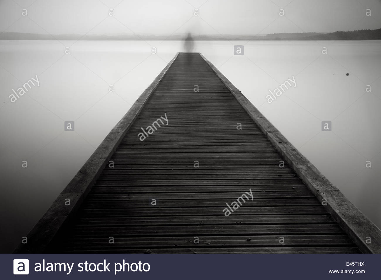 Ghostly figure on jetty. Biarritz, France, October 2010. - Stock Image
