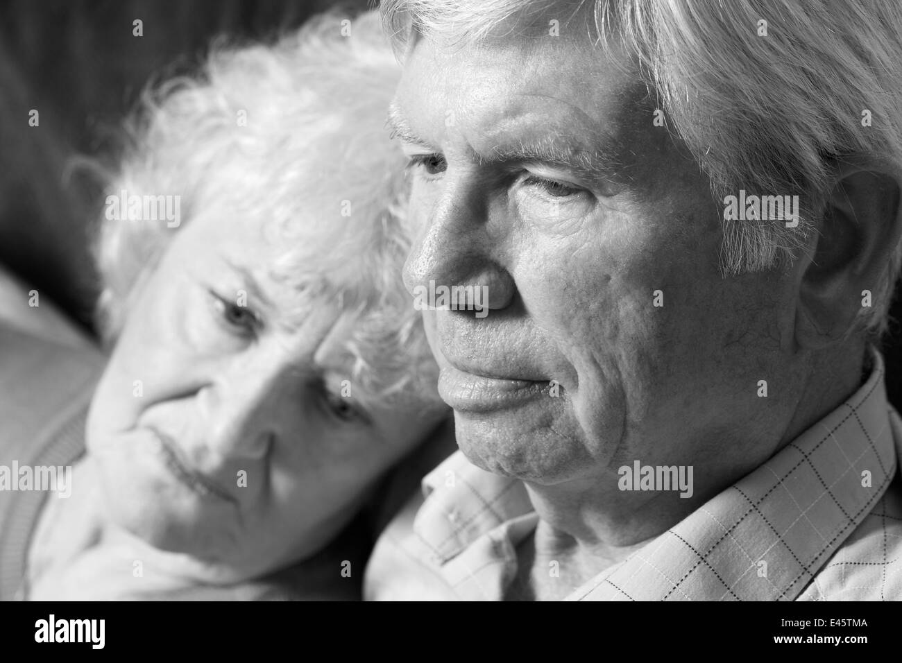 A black and white portrait of a senior couple relaxing indoors. - Stock Image