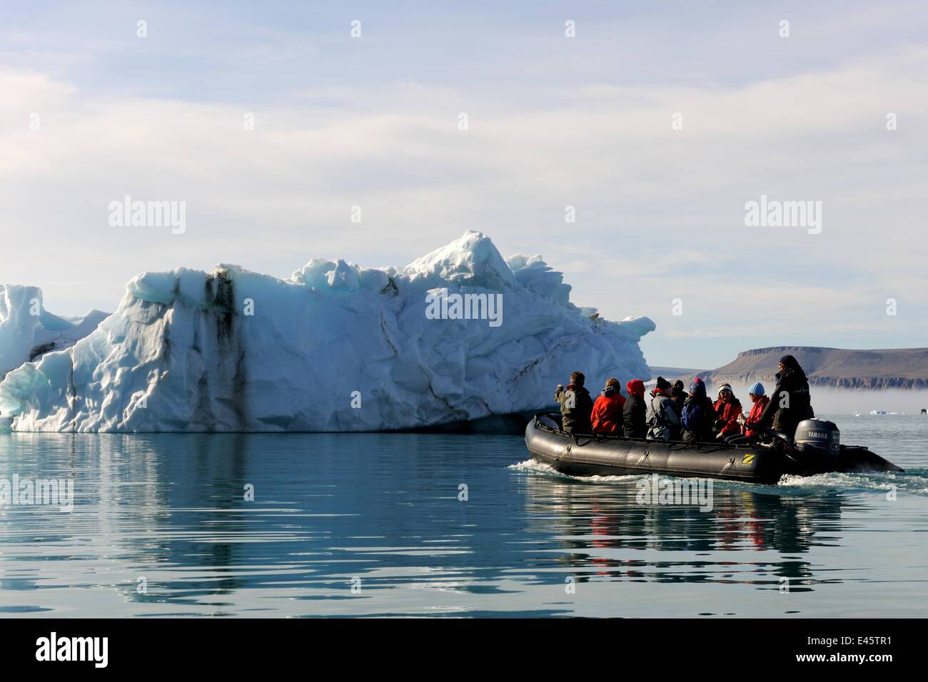 Tourists in a Zodiac rib, observing an iceberg near  Devon Island, Nunavut, Canada, August 2010 - Stock Image