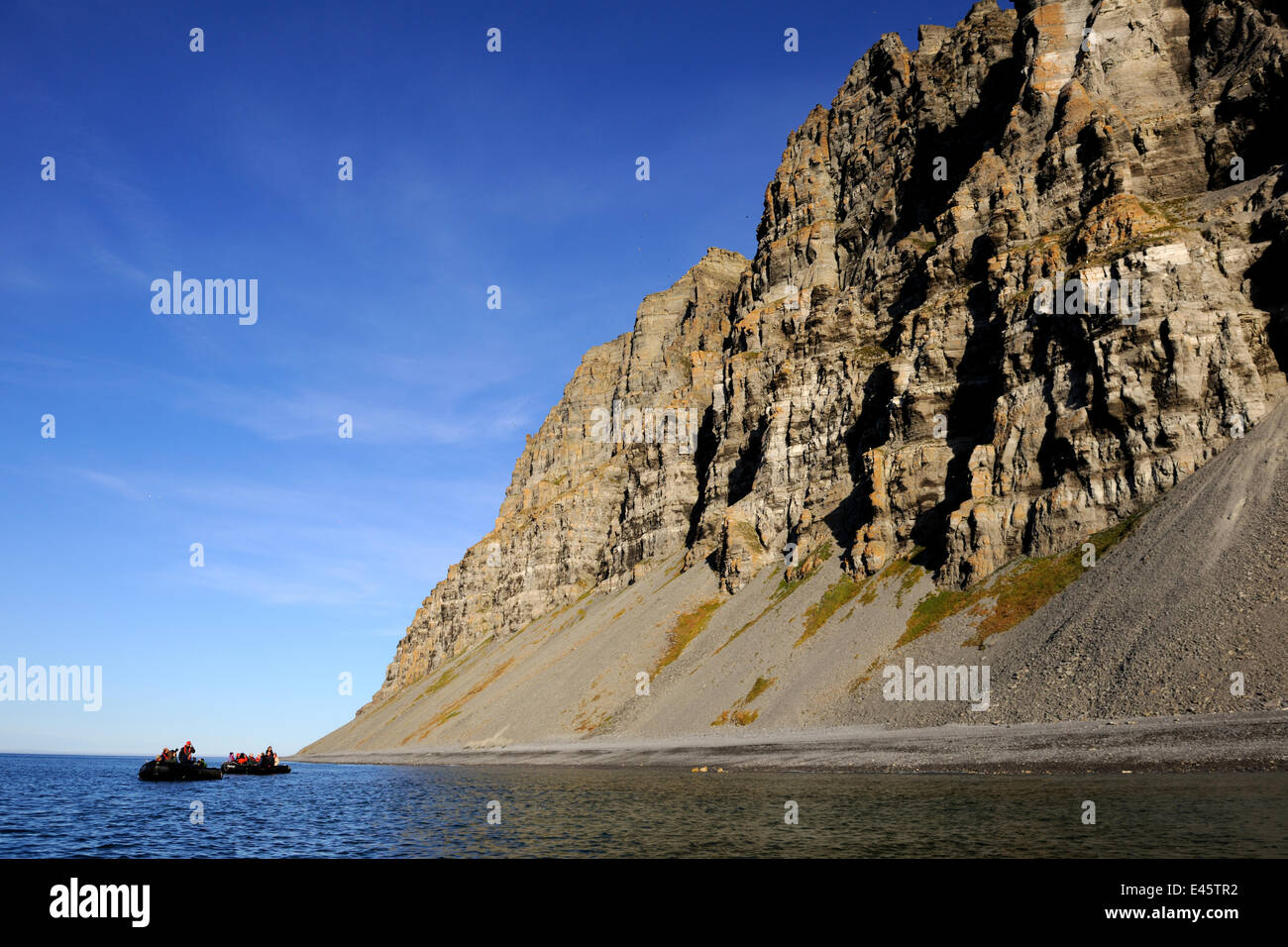 Tourists in a Zodiac rib, looking at the Liddon Cliffs   Devon Island, Nunavut, Canada, August 2010 - Stock Image