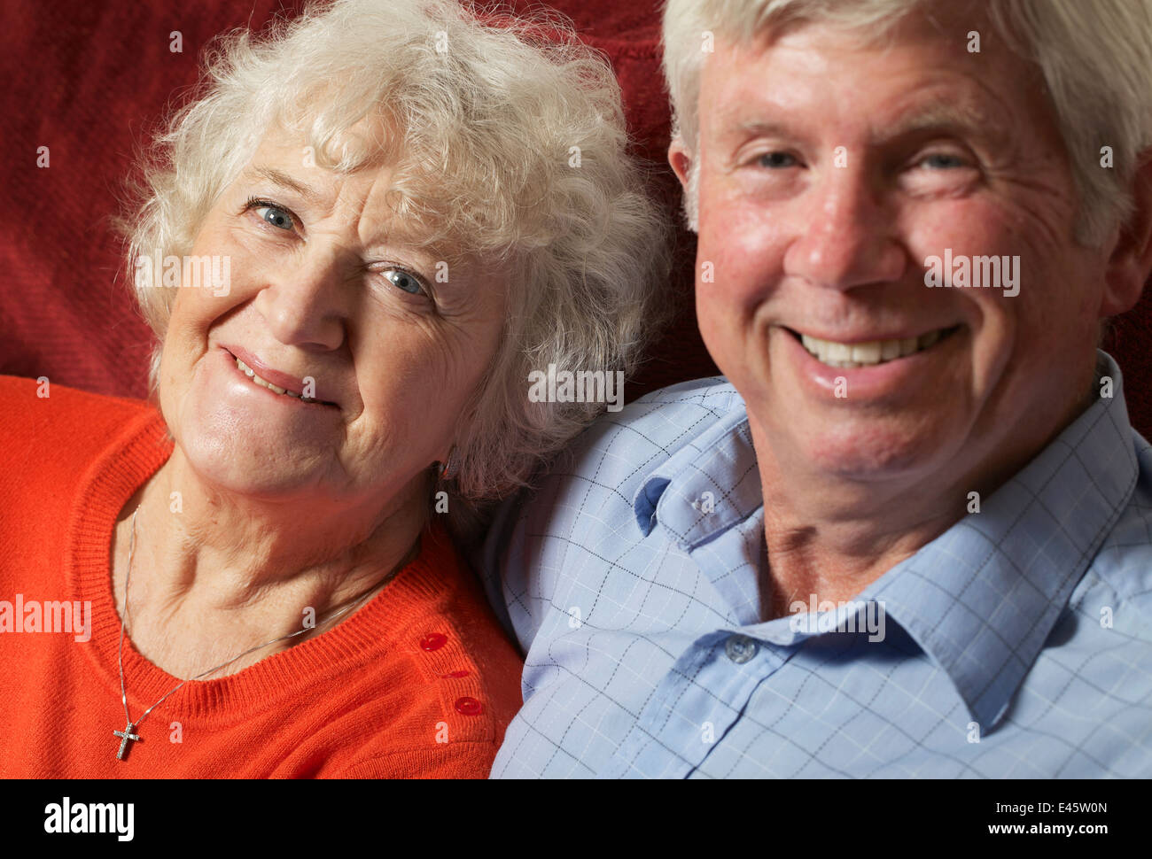 A senior couple relaxing indoors. - Stock Image