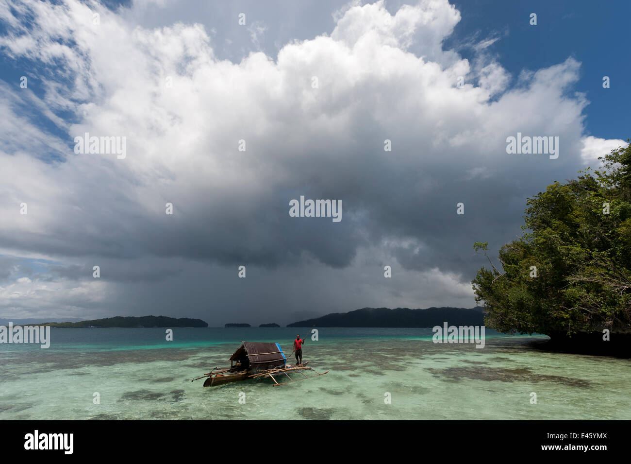 West Papuan fisherman in his outrigger house boat in the shallows over the reef. Raja Ampat, West Papua, Indonesia, - Stock Image