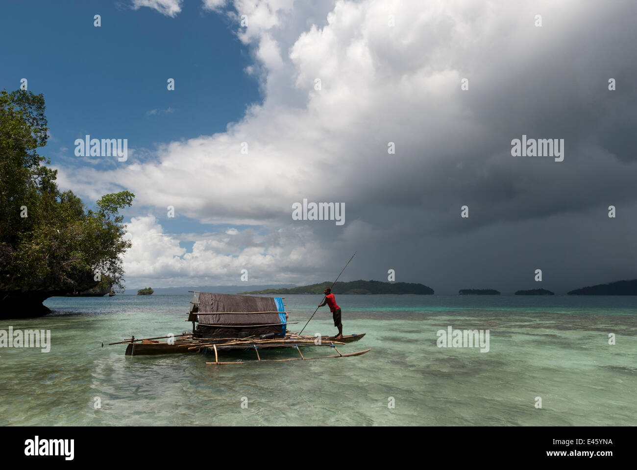 West Papuan fisherman in his outrigger house boat leaving the shallow island. Raja Ampat, West Papua, Indonesia, - Stock Image