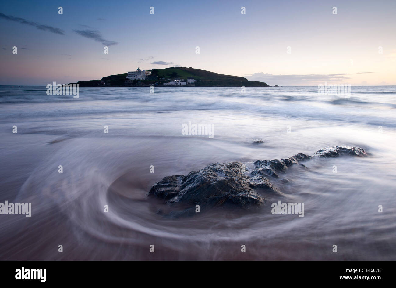 Burgh Island in the late evening light with seaweed washed onto the shore in the foreground. Bigbury-on-Sea, South - Stock Image