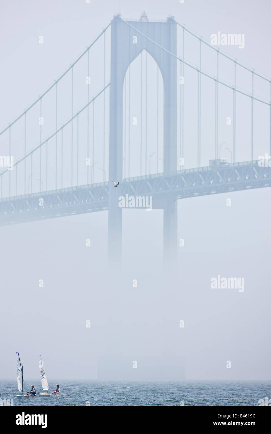Two tiny boats in the mist beneath bridge during the Optimist North Americans, Newport, Rhode Island, USA, August - Stock Image