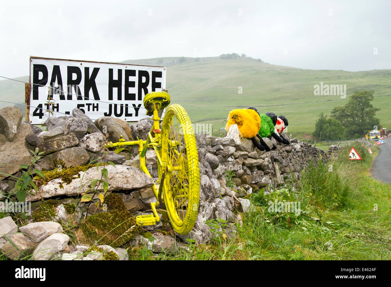 Kilnsey en-route to Kettlewell,  Yorkshire Dales, UK 3rd July, 2014.  Cycle imbedded in stone wall a decorations Stock Photo