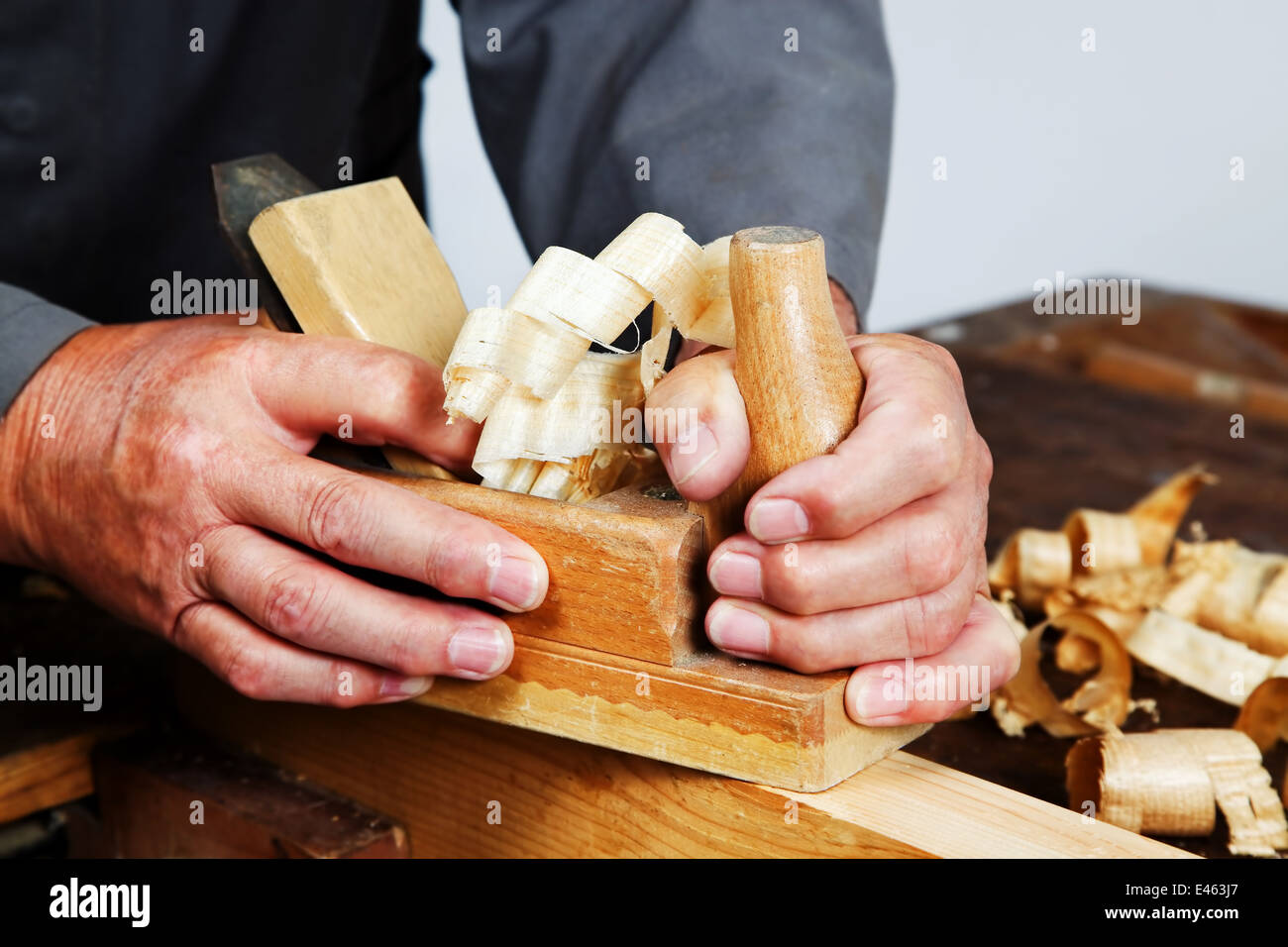 a carpenter with a planer and wood shavings in the workshop stock