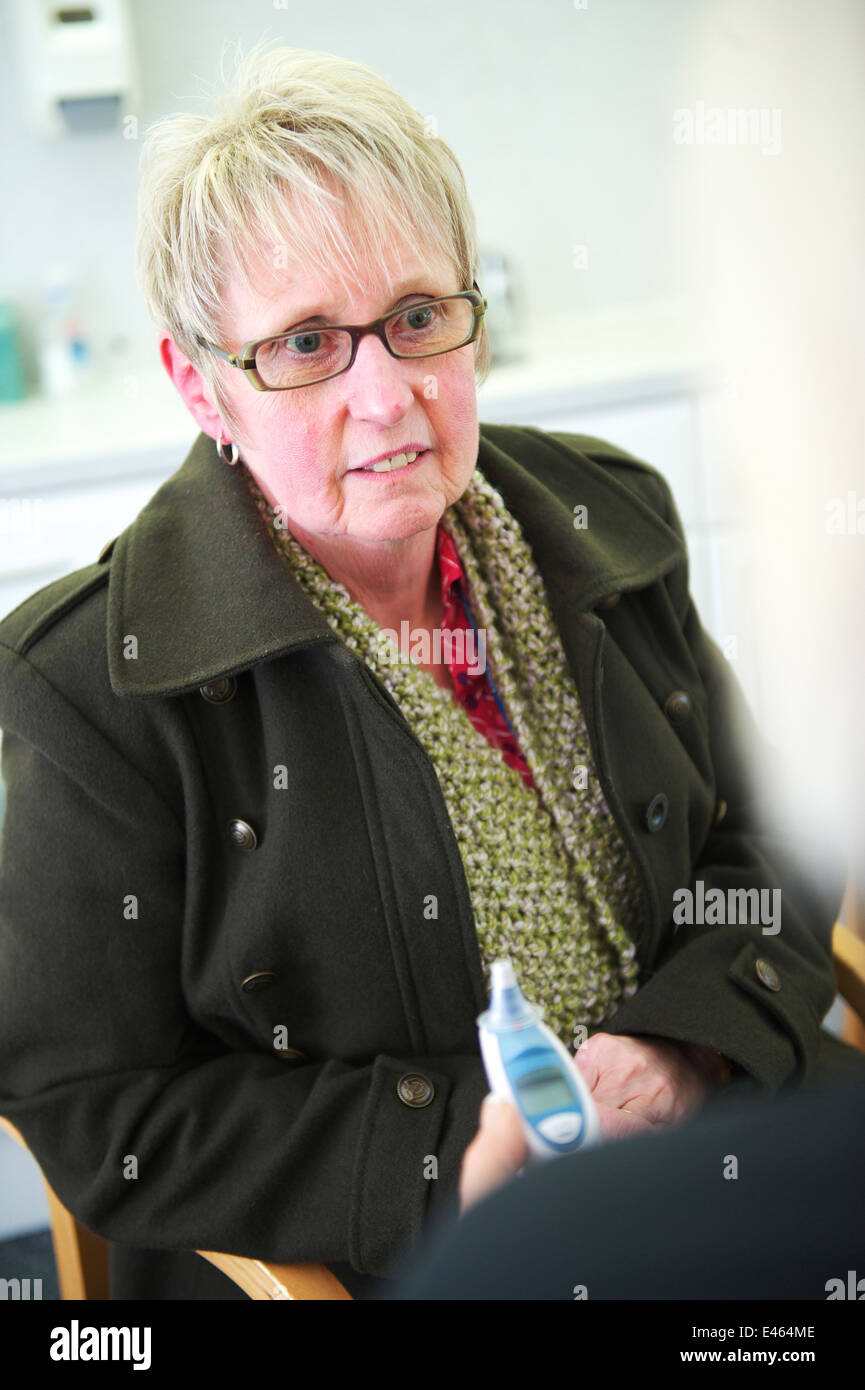 middle aged white female patient is in a consultation with her local Doctor/GP in a NHS surgery - Stock Image