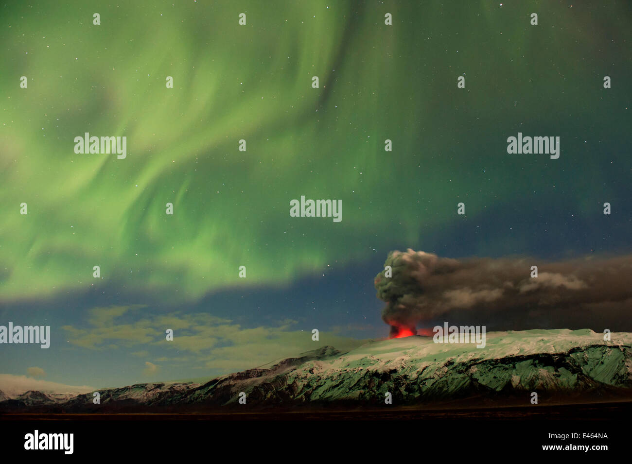 Subglacial volcanic eruption under the Eyjafjallajokull ice cap with northern lights above the ash plume at night, - Stock Image