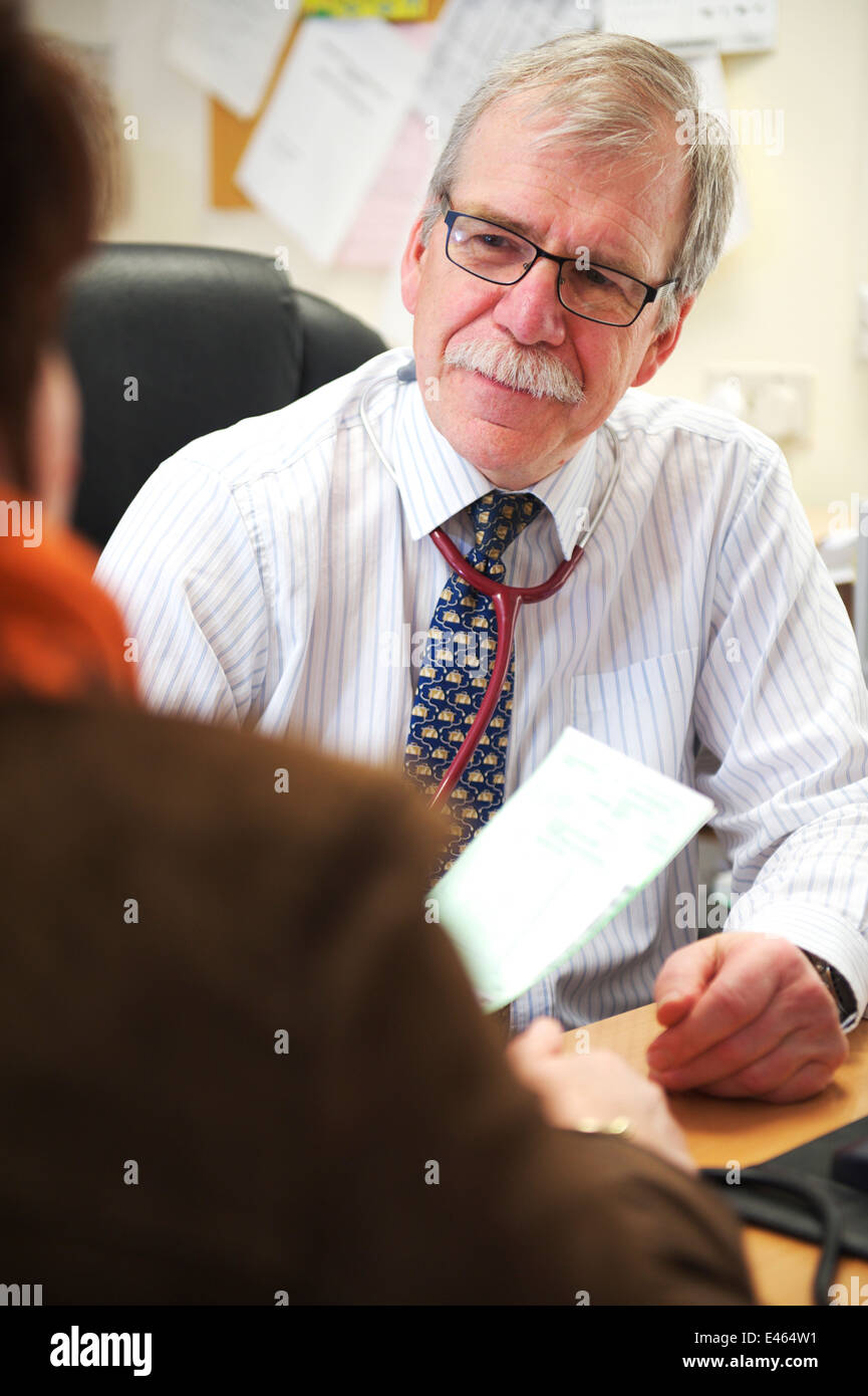 Male GP in small NHS surgery is in a consultation with a patient - Stock Image