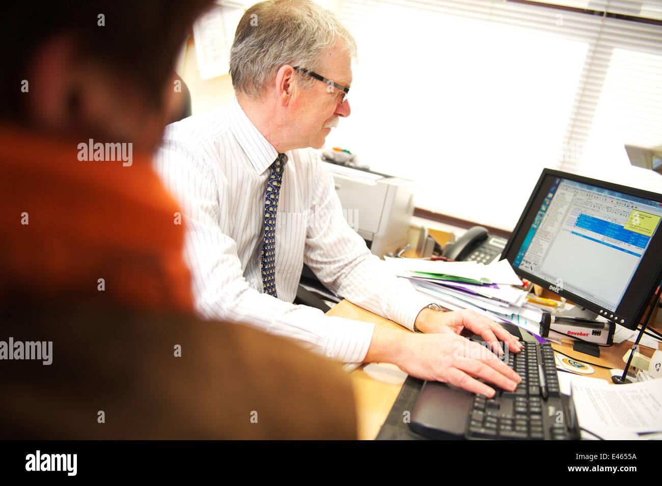 Male GP in patient consultation, looking up digital medical records - Stock Image
