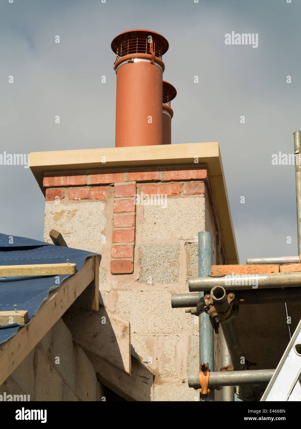 self building house, two traditional clay chimney pots with bird guard cage cowls - Stock Image