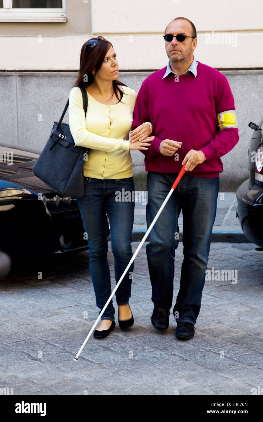 A Young Woman Helps A Blind Man Cross The Road Stock Photo