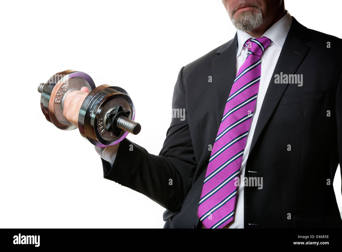 Businessman in black suit holding a silver dumbbell in the right hand - Stock Image