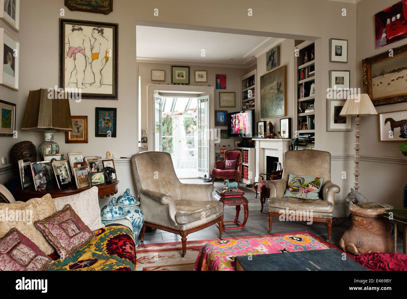 London home , shabby chic living room with velvet armchairs and cushions - Stock Image
