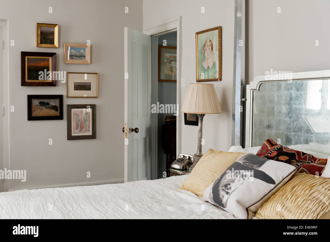 Clint Eastwood cushion on mirrored four poster bed from Julian Chichester in bedroom with assorted artwork - Stock Image