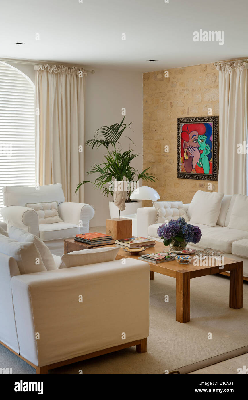 Linen covered sofas in neutral coloured living room with bright painting by Gillian Meijer - Stock Image