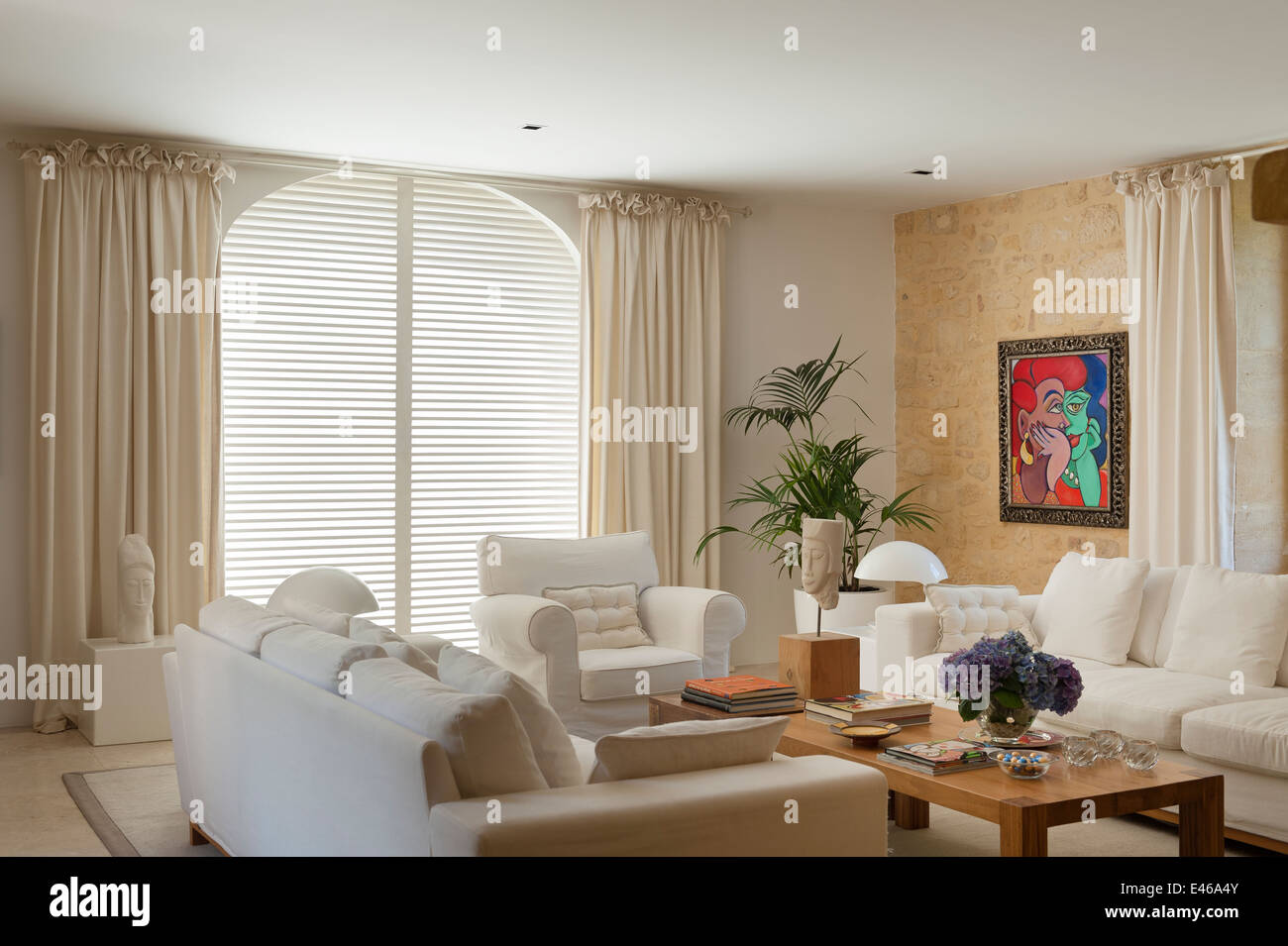 Linen covered sofas and cube side tables in neutral coloured living room with bright paintings by Gillian Meijer - Stock Image
